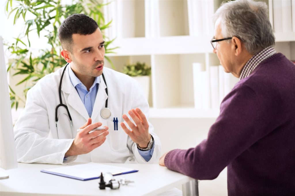 Male doctor talking with elderly man