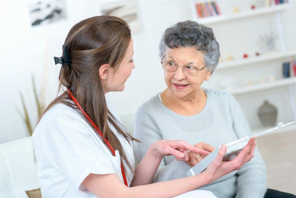 Nurse showing elderly woman something
