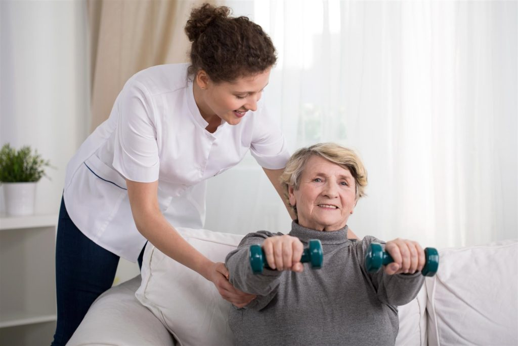 Nurse Helping Elderly Woman Lift Weights